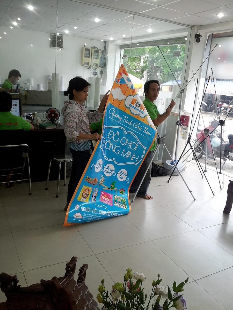 Nhân viên DVQuangCao đang tiến hành hướng dẫn khách hàng lắp đặt poster PP vào kệ standee